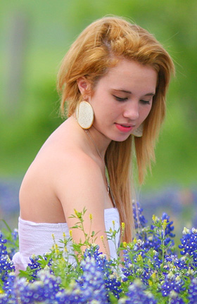 Girl gets her picture taken with Bluebonnets in Brenham Texas.